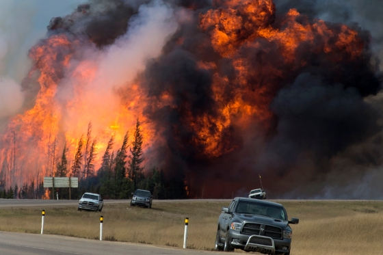 "A raging wildfire consumes the forest next to Highway 63 twenty four kilometres south of Fort McMurray Saturday, May 7, 2016. The ""Beast"", as it was called by Wood Buffalo fire chief Darby Allen, is a 1500 square kilometre inferno that has prompted the mass evacuation of nearly 90,000 people from the northern Alberta city. (photograph by Chris Schwarz/Government of Alberta)"